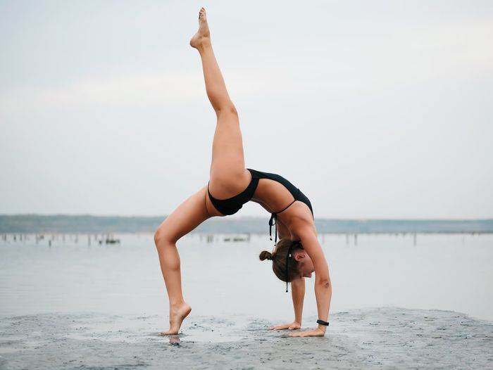 Exercising Healthy Lifestyle Balance Flexibility Yoga Only Women Vitality Full Length Lifestyles Barefoot Practicing Adult One Person Handstand  Leisure Activity Concentration Nature Young Women Bending Over Backwards Young Adult