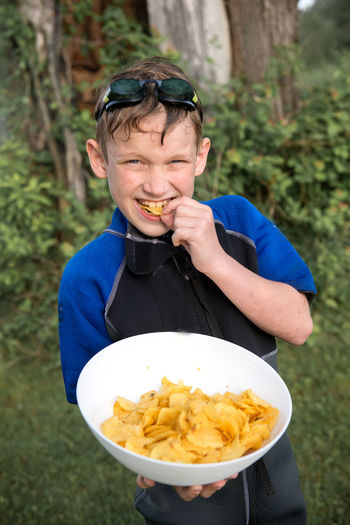High angle portrait of boy eating potato chips on field