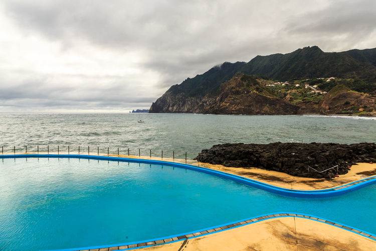Swimming pool by sea against sky