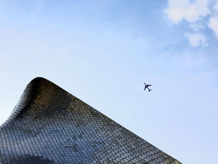 Low angle view of airplane flying over museo soumaya against sky