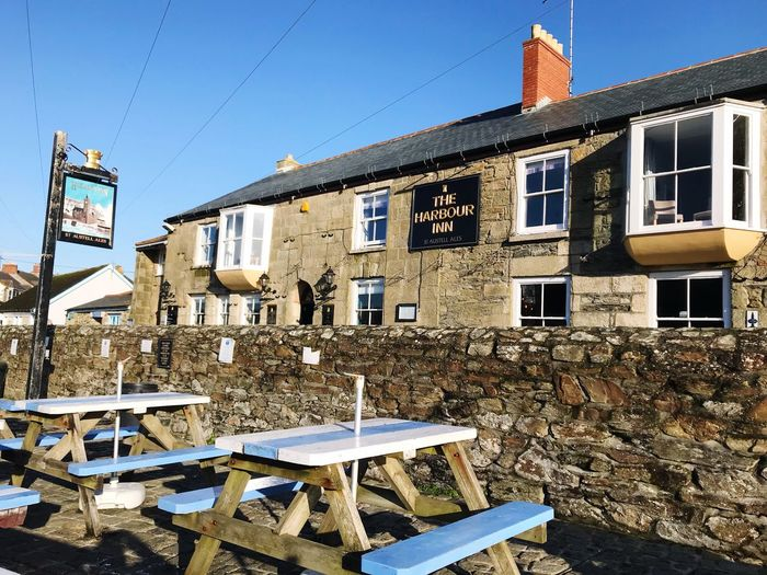 The harbour inn EyeEm Gallery Popular Destination Fishing Village The Harbour Inn Porthleven January 2018 Blue Sky On A January Day On The Harbour Benches Text Sign Pub Architecture Building Exterior Built Structure No People Day Outdoors Clear Sky
