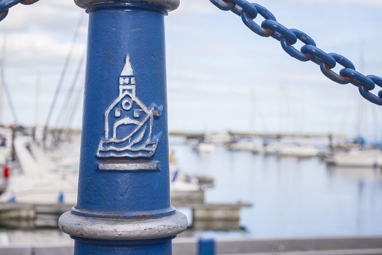 close-up of Detail marina blue pole with malahide port drawing Focus On Foreground Water Metal Day Nautical Vessel Close-up Strength Blue Connection Chain No People Transportation Architecture Outdoors Nature Harbor River Sky Mode Of Transportation Architectural Column Sailboat