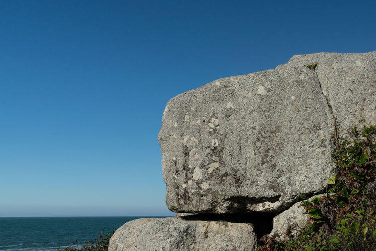Rock formation by sea against clear blue sky