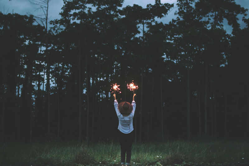 Rear View Of Woman Holding Illuminated Sparklers In Forest During Dusk