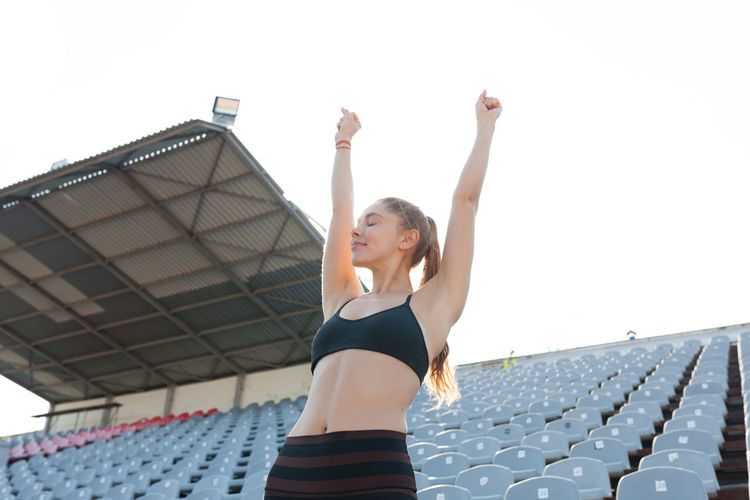 Low angle view of woman with arms raised standing against sky