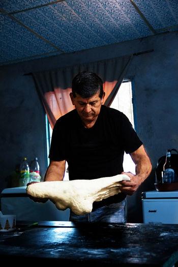 Portrait of man preparing dough for bread