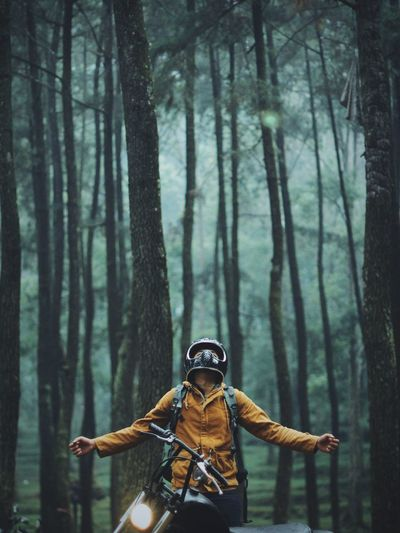 Man with motorcycle in forest