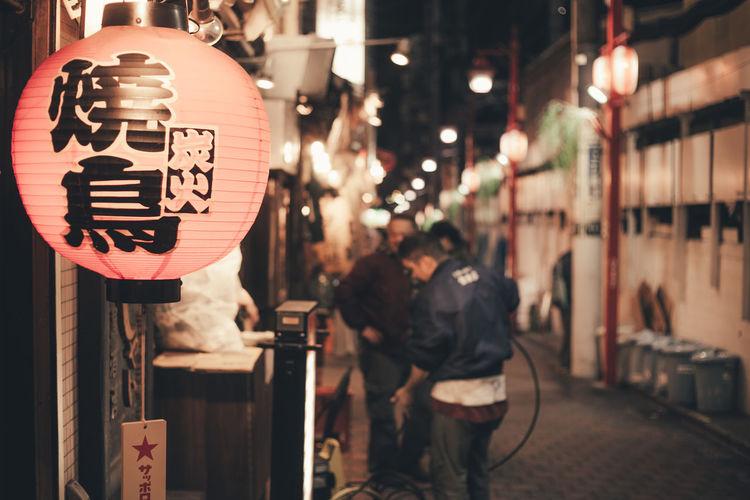 Text on illuminated lantern hanging at market in city during night