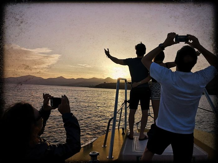 People photographing at sea shore against sky during sunset
