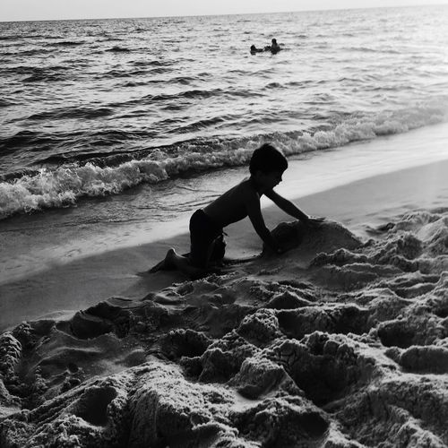 Full Length Side View Of Shirtless Boy Playing With Sand On Shore At Beach