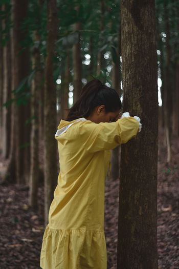 Woman standing by tree trunk in forest playing hide and seek