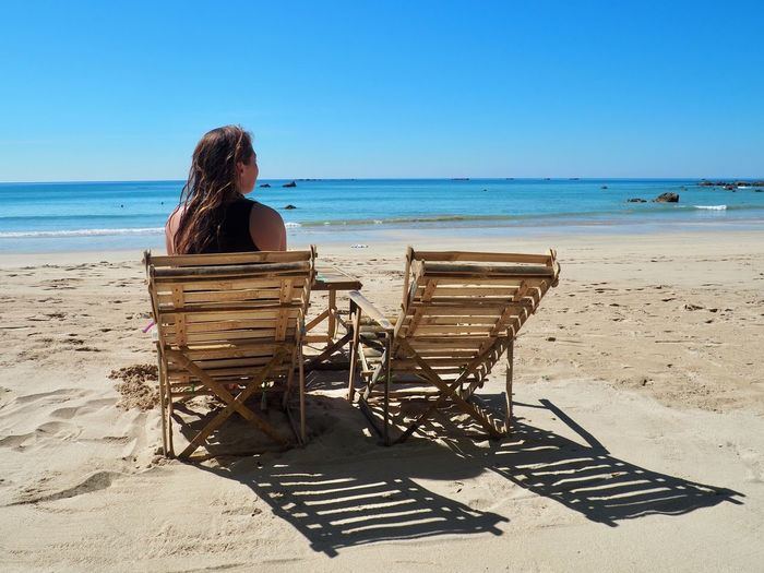 Rear View Of Woman Sitting On Beach Against Clear Sky