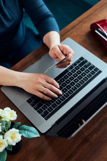 Woman doing online shopping using debit card and laptop. female hands holding credit card