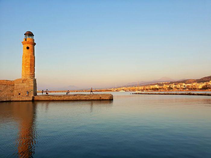 Lighthouse on building by sea against clear sky