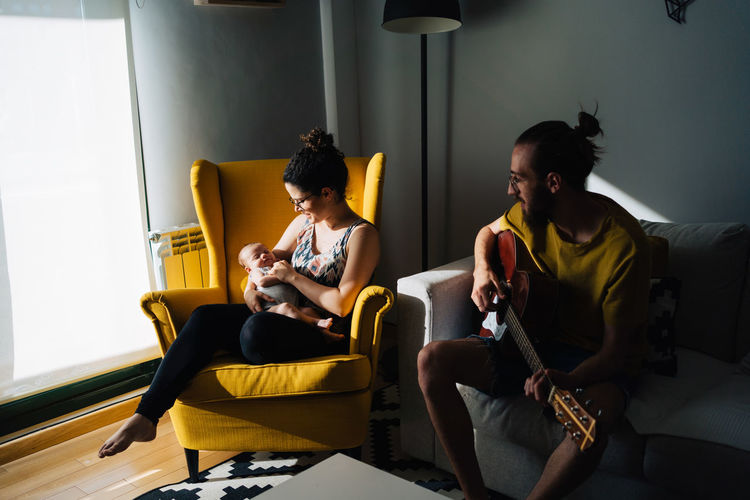 Woman sitting on yellow sofa at home holding her new born baby