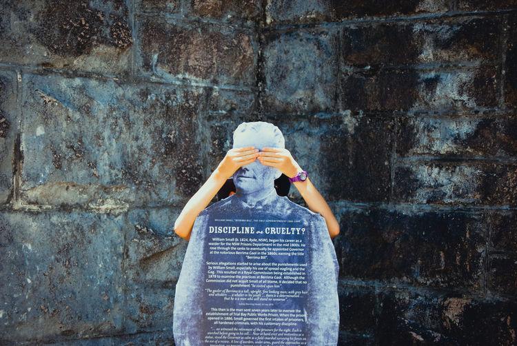 Eine kinderhand hält die augen zu einer statue