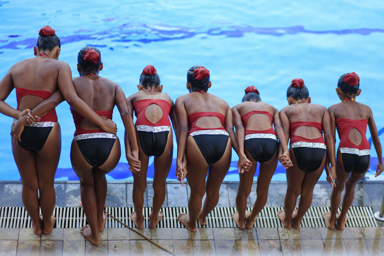 Rear view of girls standing by swimming pool