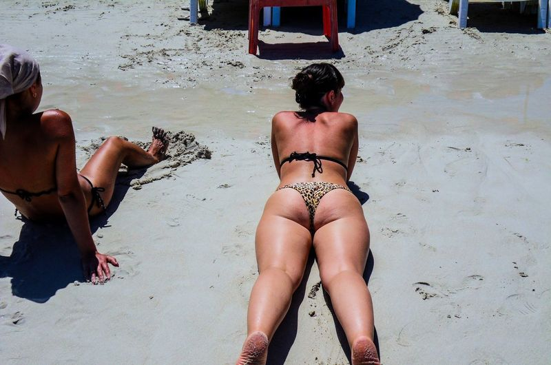 Rear view of female friends wearing bikinis at beach