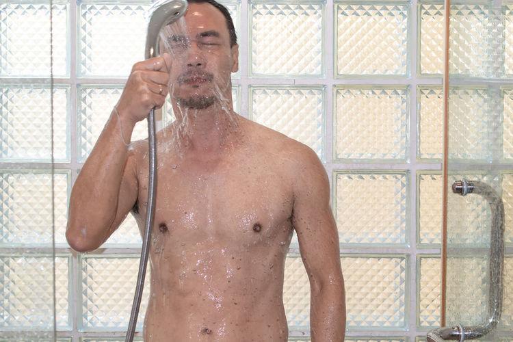 Man Taking Shower In Bathroom