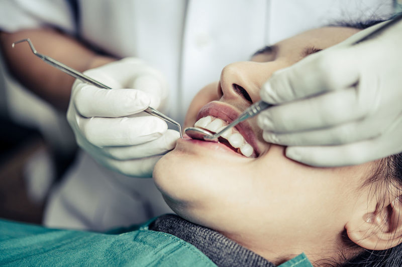 Close-up of young woman getting her teeth examined by dentist