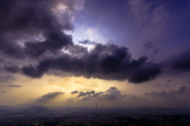 Scenic view of dramatic sky over city during sunset