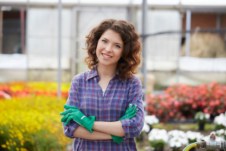 Portrait of woman with arms crossed standing in greenhouse
