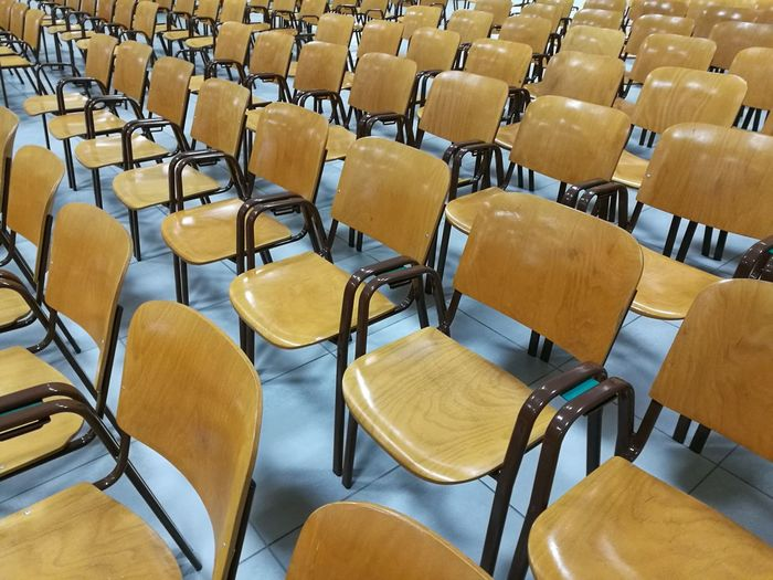 Full frame shot of empty wooden chairs at auditorium
