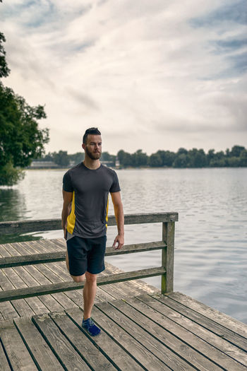 Young man doing stretching exercises on a deck Beard Bearded Deck Exercise Fit Fitness Full Length Healthy Lifestyle Lake Male Man One Man Only One Person Outdoors Park Sport Sports Training Stretching Water Wooden Young