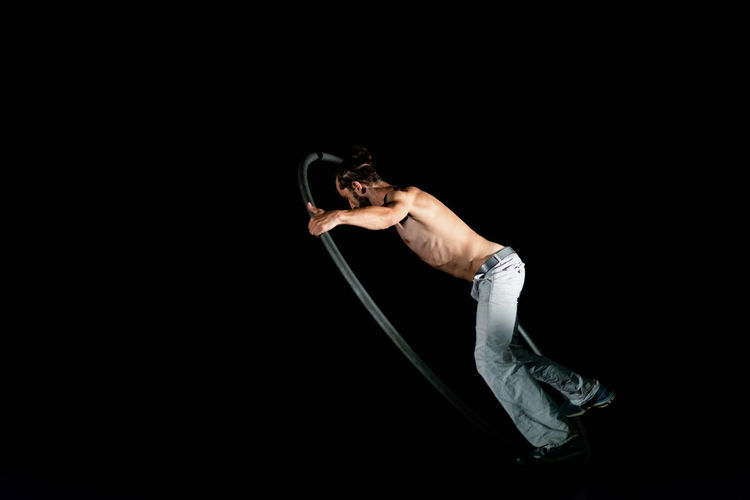 Circus Adult Arts Culture And Entertainment Balance Black Background Casual Clothing Copy Space Cut Out Flexibility Full Length Healthy Lifestyle Holding Indoors  Lifestyles One Person Performance Real People Side View Strength Studio Shot