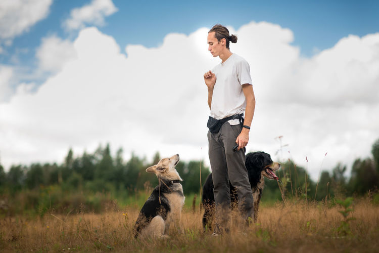Man training dogs on grassy land against cloudy sky