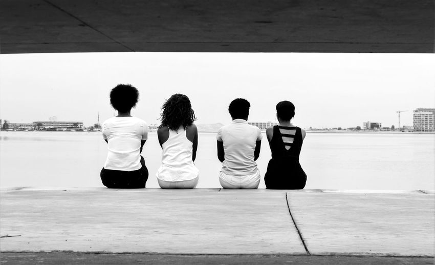 Rear view of friends sitting on jetty against sea