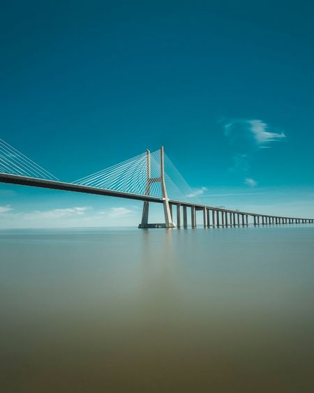 Suspension bridge over sea against sky