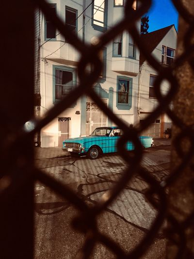 Night Dark Darkness Spotlight Street Light Vintage Car Car Blue Turquoise Colored Built Structure Architecture Building Exterior Building Window No People 17.62° Fence Shadow Chainlink Fence Metal Residential District Focus On Background Safety Security Barrier Protection Boundary City Streetwise Photography