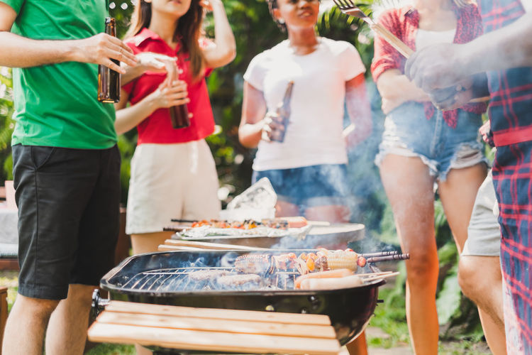 People standing on barbecue grill