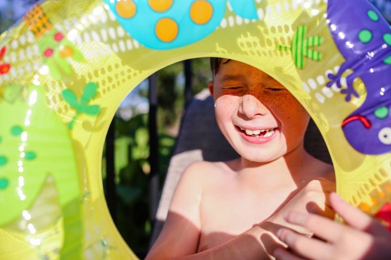 Boy crying while holding inflatable ring