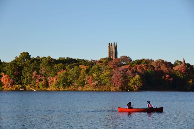 Women Canoeing On Lake Against Clear Sky During Autumn