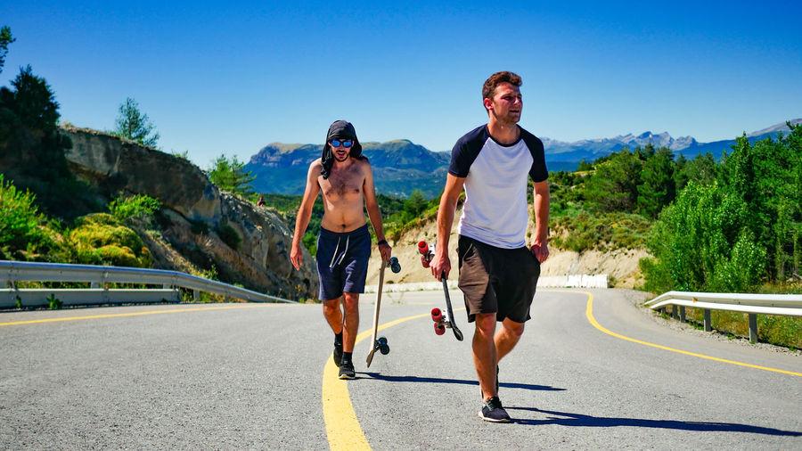 Male Friends Carrying Skateboards On Road