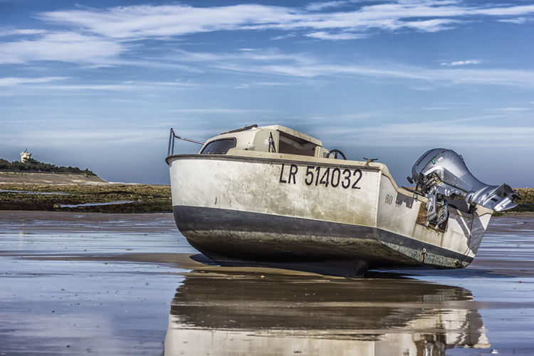 Boat moored at beach against sky