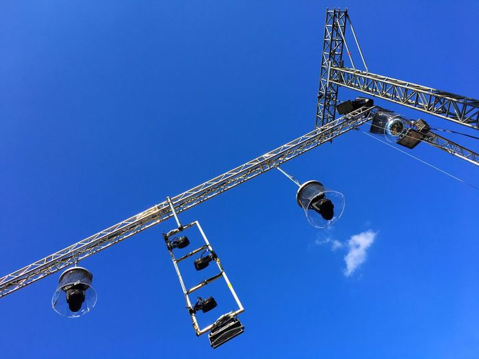 Low Angle View Of Stage Lights On Construction Frame Against Blue Sky