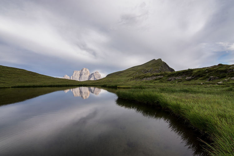 The surreal sky above Baste Lake and the Pelmo mount in the background. Tranquil Scene Scenics - Nature Grass Nature Reflection Beauty In Nature Water Green Color No People Environment Cloud - Sky Tranquility Landscape Non-urban Scene Lake Sky Day Mountain Plant Outdoors Dolomites, Italy Dolomites