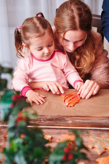Mother and daughter preparing gingerbread cookies at home