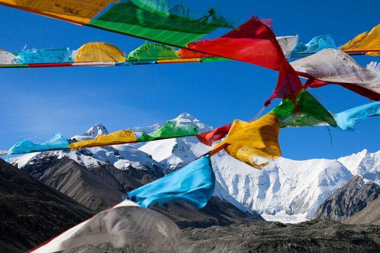Spiritual buntings hanging on mountain against sky