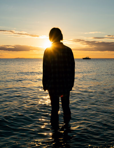 Teenager standing in calm ocean water at sunset with a warm glowing sky