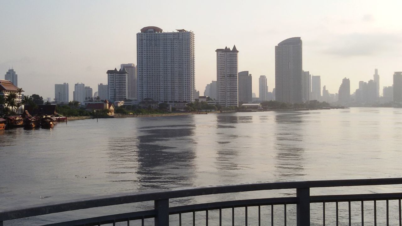 skyscraper, architecture, city, building exterior, built structure, cityscape, tall - high, urban skyline, water, modern, tower, railing, river, downtown district, waterfront, sky, outdoors, day, travel destinations, no people