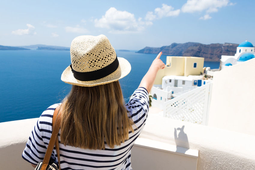 Santorini Casual Clothing Day Finger Greece Hat Leisure Activity Lifestyles Mobile Phone Mountain One Person Outdoors Photography Themes Portable Information Device Real People Rear View Santorini Sea Selfie Smart Phone Sun Hat Sunlight Vacations Water Wireless Technology Women