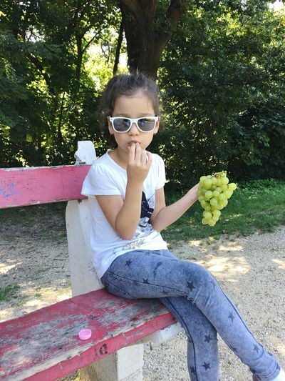 Girl Eating Grapes While Sitting On Bench