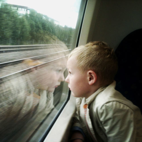 Young boy on a train looking through the window. Boys Child Childhood Innocence Journey Looking Looking Through Window One Person Rail Transportation Transportation Window