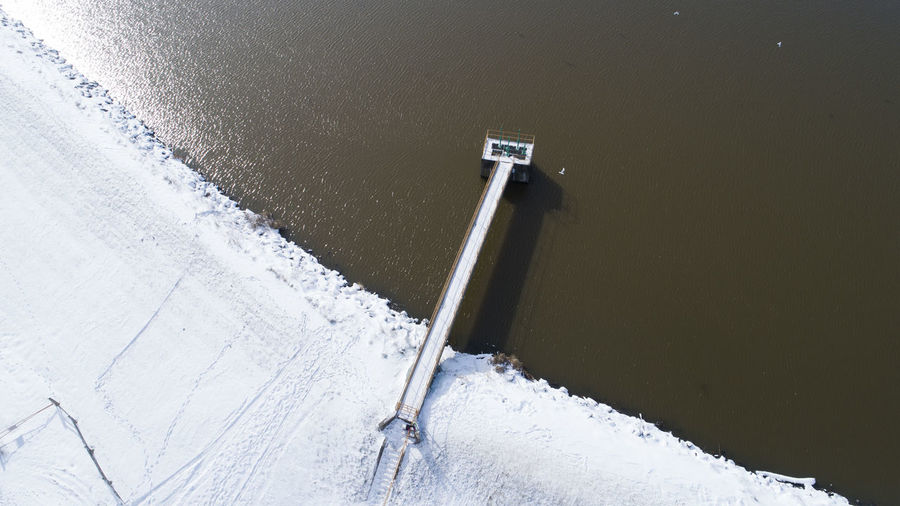 Winter sets in around the Carbondale water reservoir that sits outside the city. Snow Winter Cold Temperature No People White Color Day High Angle View Nature Water Outdoors Sea Covering Beauty In Nature Frozen Built Structure Land Close-up Reservoir Waterfront Winter Bridge Illinois Carbondale, Illinois Water Source Aerial View