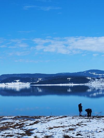 Men fishing while standing by lake during winter