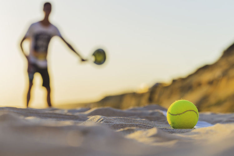 Martian defocused playing tennis, tennis ball focused on foreground Selective Focus Ball Tennis Sport Close-up Tennis Ball No People Yellow Representation Still Life Sphere Human Representation Day Nature Sports Equipment Green Color Outdoors Sky Figurine  Surface Level Accessory Active Activity Beach Competition Competitive Concept Exercise Forehand Game Health Hobby Individual Leisure Lifestyle LINE Martian  Match Play Playing Racket Sand Shot Single Summer Sunny Sunset Tennis Tennis Ball Outdoor